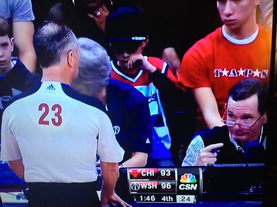 A referee confers with PA announcer Mike Clapper at the scorers' table in this photo taken off a broadcast of a Washington Wizards game.