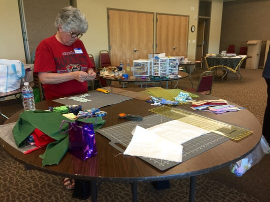 A volunteer cuts out fabric for quilts Saturday, May 9, for Alexia's Cozy Covers, a nonprofit that donates blankets for youth and families in need.