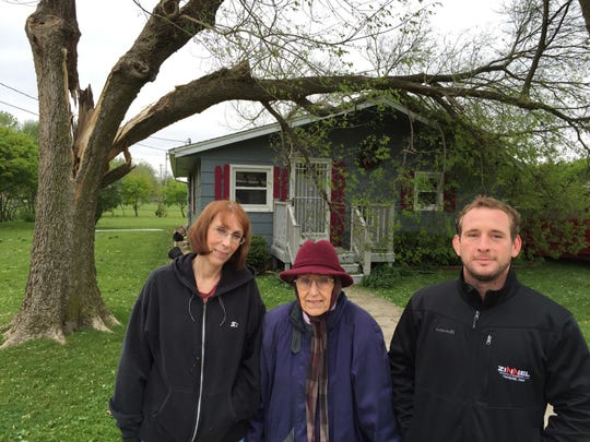 From left, Marsha Berry, her mother Mary E. Seufferlein, and roofing contractor Curt Zinnel stand in front of Seufferlein's house in Lake City, Ia., on Monday. The house was reroofed Saturday, and a tornado slammed a tree across it the following day. An EF1 tornado swept through town on Sunday.