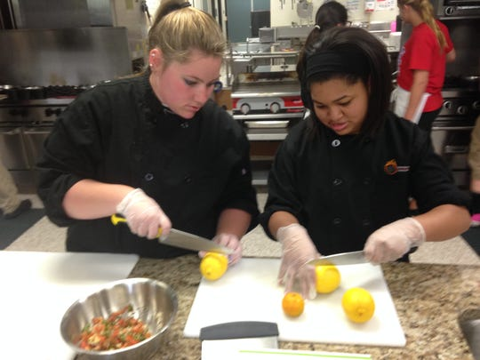 Kelsey Parsons (left) and Erayna Greenwood cut up lemons and limes Friday at the Capital Area Career Center in Alaiedon Township.