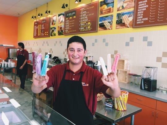 """Tabor a Tocumbo oowner Mauricio Rosales displays a few of the popsicle offerings """"Wolverine Style."""""""