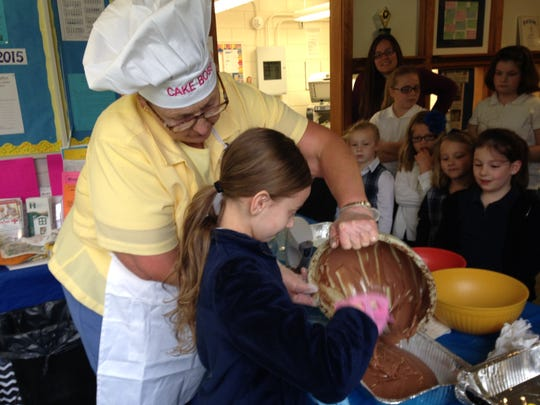 St. Edward on-the-Lake Catholic Elementary School Principal Nancy Appel enlists the help of fourth-grader Tiffany Hopkins and other students to bake cakes for the entire school on Wednesday. Students earned the cakes for exceeding a reading challenge from Appel.