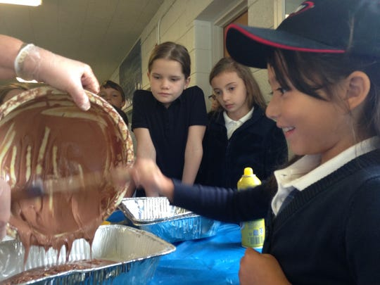First grader Isabella Levitte-Mendoza helps Principal Nancy Appel bake cakes at St. Edward on-the-Lake Catholic School in Lakeport while her fellow students look on.
