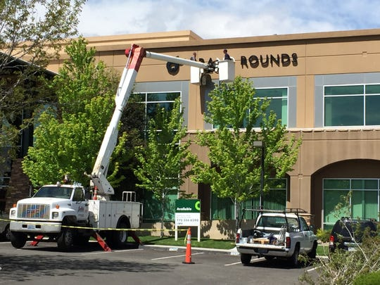 Workers put the finishing touches on Grand Rounds signage at its new Sierra Patient Center in south Reno.