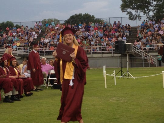 Kelly Stewart smiles for pictures as she walks back to her seat with her diploma during Crockett County High School's graduation. Kelly and Kasey Stewart were named valedictorian and salutatorian of their graduating class.
