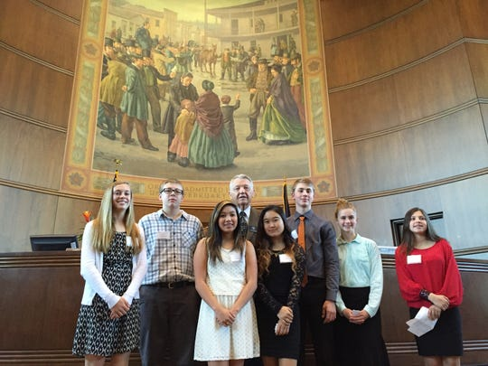Chuck Bradish (back center) takes a moment to get a group photo with students participating in the Oregon Senate's honorary page program on Thursday, April 20, 2015.