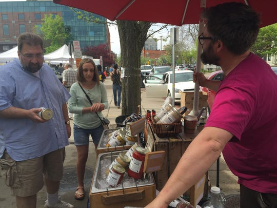 The Brinery is a vendor at Ann Arbor's outdoor farmer's market. David Klingenberger, on the right, serves customers.