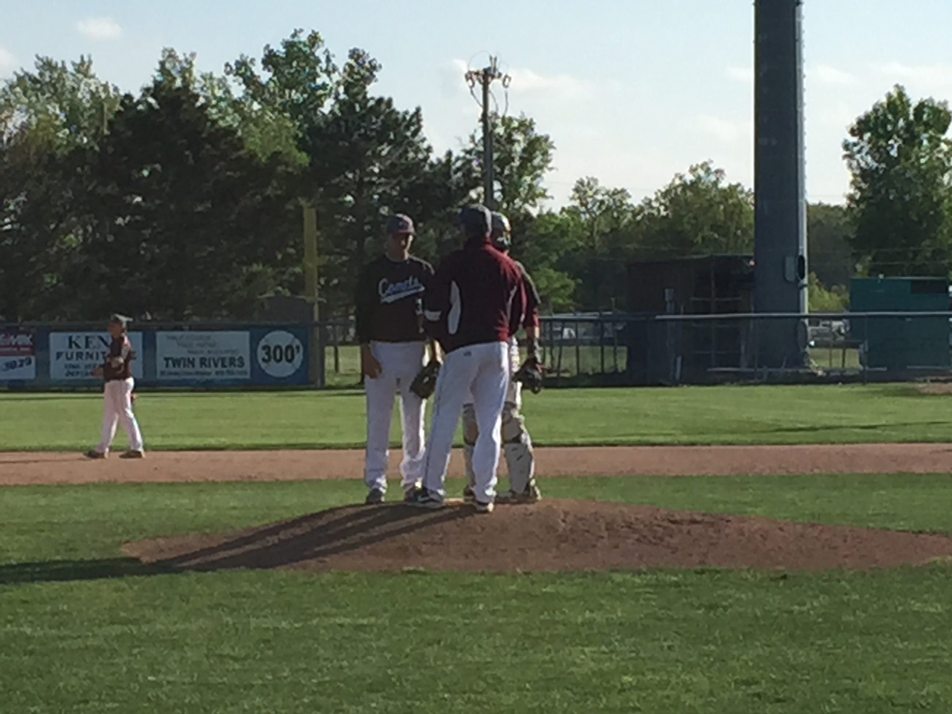 Genoa coach Ron Rightnowar visits pitcher Luke Rightnowar on the mound with two outs and the bases loaded in the top of the seventh inning Thursday against Sherwood Fairview.