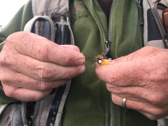 Guide Mike Sexton from Reno Fly Shop ties a fly to a leader during a fly fishing lesson at Idlewild Park in Reno.