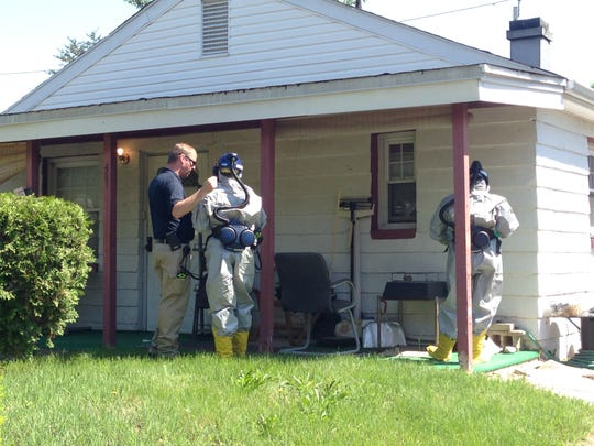 DNREC workers in protective gear were seen outside the Dunleith home in the 400 block of Morehouse Drive before entering the residence as part of an investigation to figure out what exactly sickened two of the residents and killed another.
