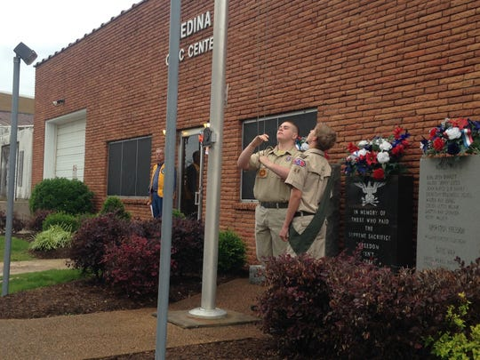 Members of Boy Scout Troop 48 lower the flag to half staff at Medina Civic Center on Monday, May 25, 2015 during the annual Lion's Club Memorial Day service.