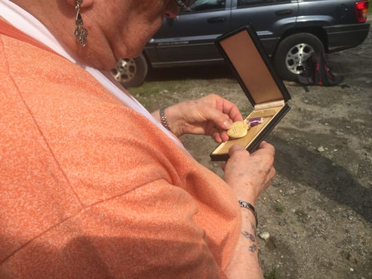 Dorothy Wescom, 74, touches the Purple Heart medal that was given to her family after her father's death in World War II. Cedric C. Laraway was killed in action in 1944.