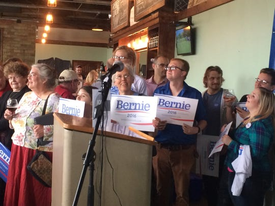 Audience members hold supporting signs for Bernie Sanders at his appearance in Ames on Saturday.