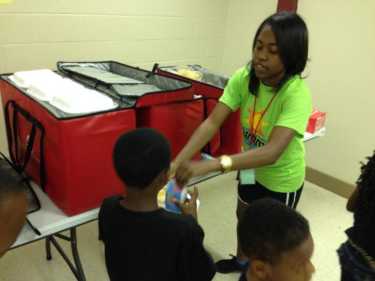 Counselor DaNielle Dykes of Alexandria hands out food to a child at Alexandria's Summer Day Camp on Monday. This is a summer job for Dykes, who is studying criminal justice and social work at University of Louisiana at Monroe.