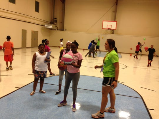 Shavon Tucker (holding basketball), 11, gets tips on shooting baskets from counselor Chelsea Evans (right foreground) at the city of Alexandria's Summer Day Camp, which opened for the summer on Monday.