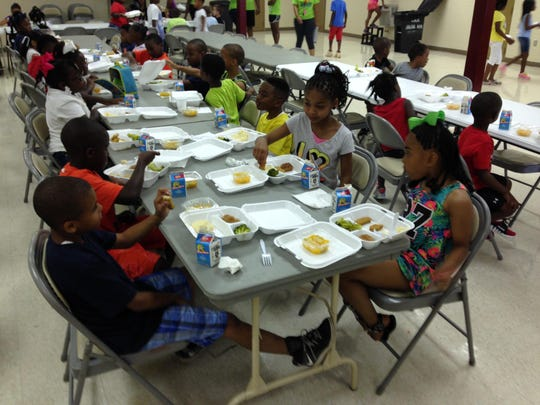 Children at the city of Alexandria's Summer Day Camp eat lunch on the camp's opening day. In foreground are Jamariel Smith (left), 8; Ethan Richard (second from left), 7; Makenzie Hamilton (right), 6; and Roye'l Roberts (second from right), 8. Lunch, which included chicken strips, mashed potatoes and broccoli, was brought from Alexandria Middle Magnet School.