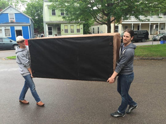 University of Vermont senior Lucas Hall, left, and recent graduate Stewart Dunoskovic move a couch into their Hyde Street apartment Monday afternoon.
