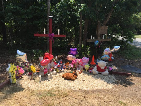 A memorial sits at the site of a fatal crash at University