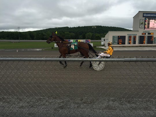 A driver stretches out a horse before a race at Tioga Downs.