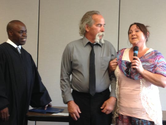 Sobriety Court graduate Jim Harper (center) watches as his wife, Donna Dora, praises the program and her husband's success. Judge Donald Allen of the 55th District Court looks on at left.