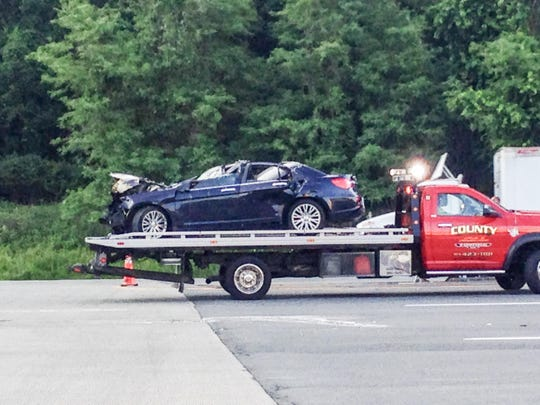 A Chrysler sedan is removed the scene of a crash with a tanker truck on the Thruway in Yonkers at the toll booth Wednesday morning, June 10, 2015