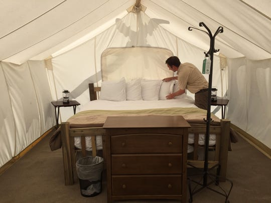 Eric Otis, general manager at Yellowstone Under Canvas, arranges pillows on a bed inside a luxury camping tent.