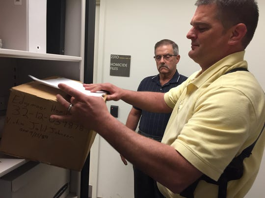 New Castle County police Cold Case Unit investigators Glenn L. Davis (left) and Detective Thomas Orzechowski inspect files. Davis returned to investigative work after his first retirement following 20 years on the force and his second retirement after 20 years running his family's business.