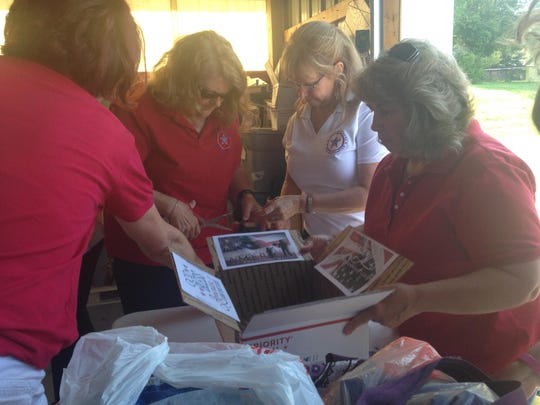 Peggy Brown (second from left) works with others members of Blue Star Mothers Chapter 99 to pack care packages for deployed troops on Wednesday, June 10.