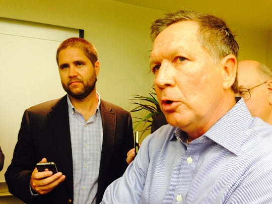 Ohio Gov. John Kasich speaks with reporters in Lansing on Tuesday