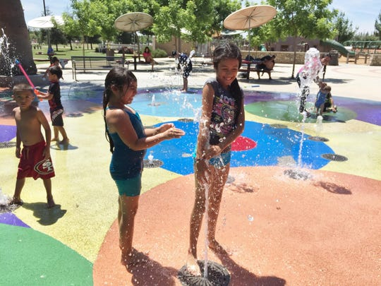 Dayanara Varrera, 7, left, and her cousin, Genesis Villa, 9, both of Cutler, ended an abnormally hot spring season in the Valley on Saturday by keeping cool at the splash pad at Riverway Sports Park in Visalia. Temperatures that day reached 102 degrees in the city.