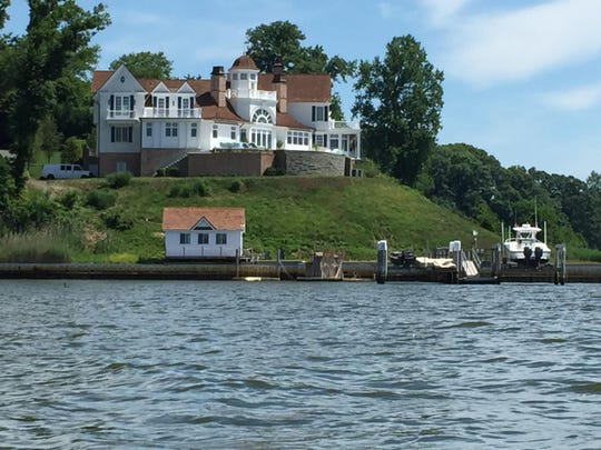 A mansion with a steeply pitched lawn overlooking the Navesink.
