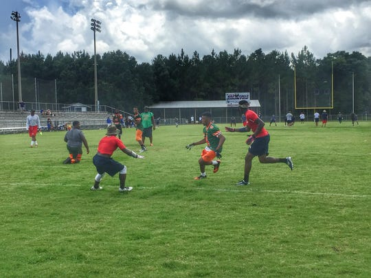 FAMU DRS rising senior receiver Chris Jackson runs a route between Wakulla defenders Antonio Morris (left) and Keith Gavin (right) during last Saturday's 7-on-7 tournament in Wakulla.