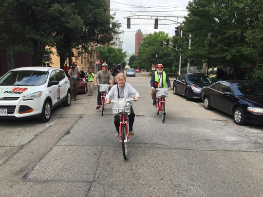 Then- Covington Mayor Sherry Carran, center, Roebling Point Bookstore owner Richard Hunt, left, and Red Bike board member and Queen City Bike president Frank Henson ride Red Bikes in Covington.