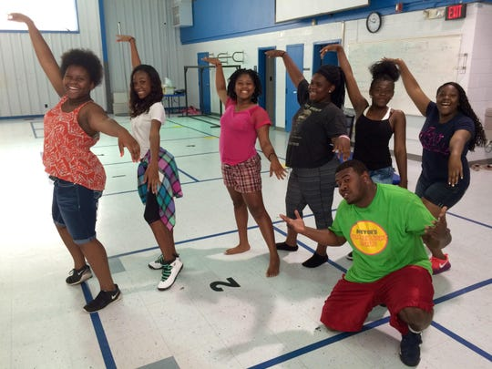 Director Eric Purvis, front, cuts up with teenage girls at Moore Elementary School. All of the girls receive free dance instruction as part of the city's free Summer Youth Program.
