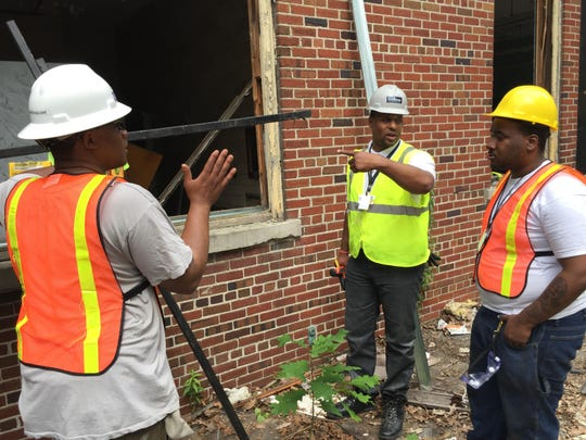 Rodney Prater, center, a general manager for Detroit-based Jenkins Construction, teaches young people the ins and outs of carpentry on Tuesday, June 30, 2015.