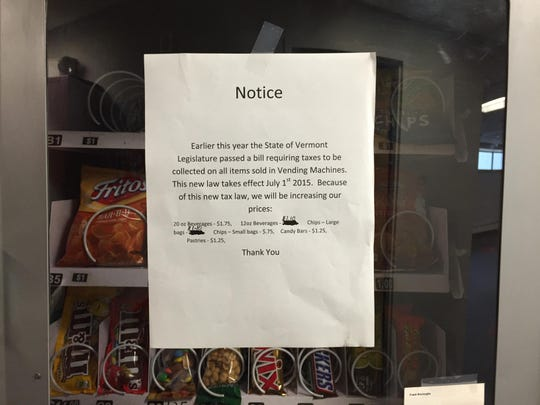 A sign on a Break Time Vending machine at downtown Burlington's 100 Bank St. building informs customers of a price increase associated with the new 9-percent meals tax on vending machine items.