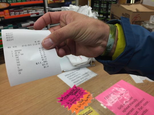 South Burlington resident Steve Grimm holds up a receipt for a soft drink he bought Wednesday at Kerry's Kwik Stop in Burlington. The receipt shows a sales tax of 12 cents on a 20-ounce soft drink, which cost $1.89.