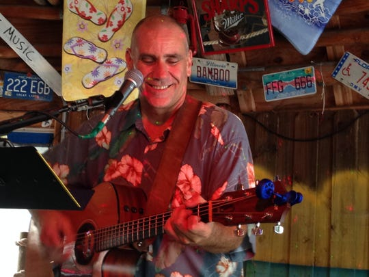 "Scotty Bryan sings trop-rock music at the happy hour in the Paradise Tiki Hut Bar & Grill where the Southwest Florida Parrot Head Club holds one of its ""phlockings."""