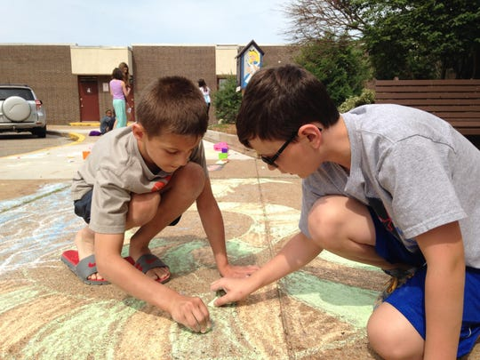 """Students Brandon Zeroik, left, and Owen Rattle work on a drawing of a serpent dragon. """"We couldn't decide between a snake and a dragon,"""" Zeroik said. Zeroik will be in 6th grade this fall and Rattle will be in 7th."""
