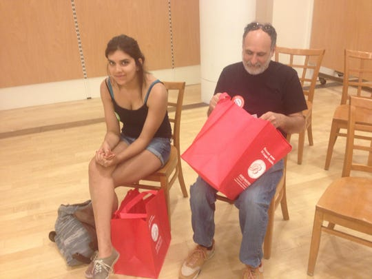 Fred Lavenberg of Jericho checks the goodies in the free gift bag provided blood donors Friday at Burlington Town Center. Aliya Khan, left, also waits to donate blood after bicycling into Burlington from South Hero.