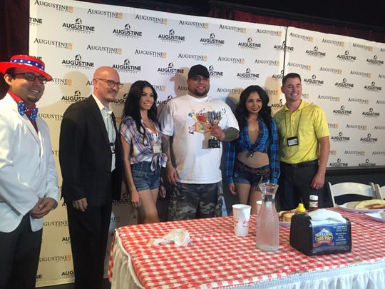 John Luis Rivera poses with Augustine Casino staff after winning the second annual hot dog eating contest.