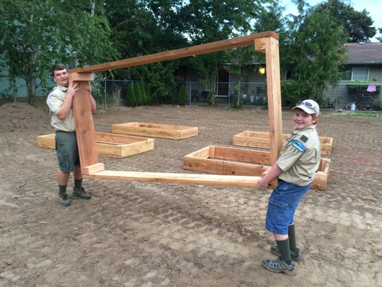 Teegan LaRochelle, left, and a Boy Scout help move a garden bed for Nuestra Casa's community garden. LaRochelle took on the construction of the garden for his Eagle Scout project.