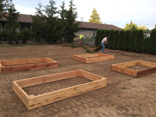 Garden beds are placed on the site of the community garden coming to Nuestra Casa, 924 Arthur Way NW.