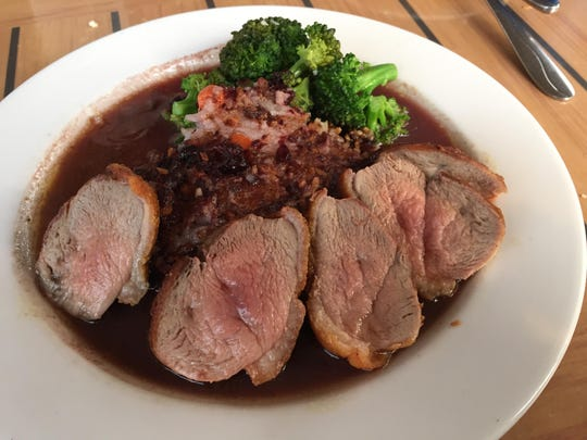 Pan-seared duck breast with boysenberry bacon jus is served with crispy sticky rice cake and broccoli at the Pultneyville Grill.