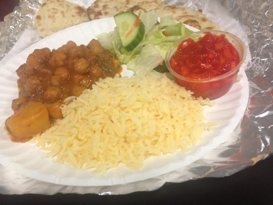 Aloo chole curry from India Palace, spiced hot, served with salad, naan, rice, and a tomato onion chutney.