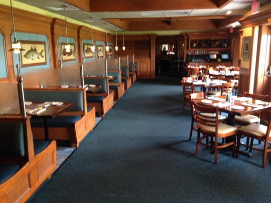 The wood paneled walls create a cool, classic dining environment for guests at The Prawnbroker in Fort Myers.