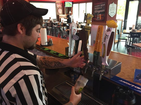 A Pizza Hut bartender pours a draft beer at the new