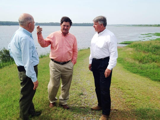 Julius Johnson, commissioner of agriculture, and state Sen. Ed Jackson discuss flooded farmland with local farmer Jimmy Hester.
