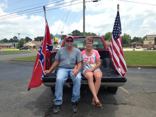 Steve and Beverly Oswalt sit in the back of their truck on Sunday, July 12, at AutoZone in Camden. The couple were part of a rally, organized by Confederate Warriors, to protest changing the name of Nathan Bedford Forrest State Park.