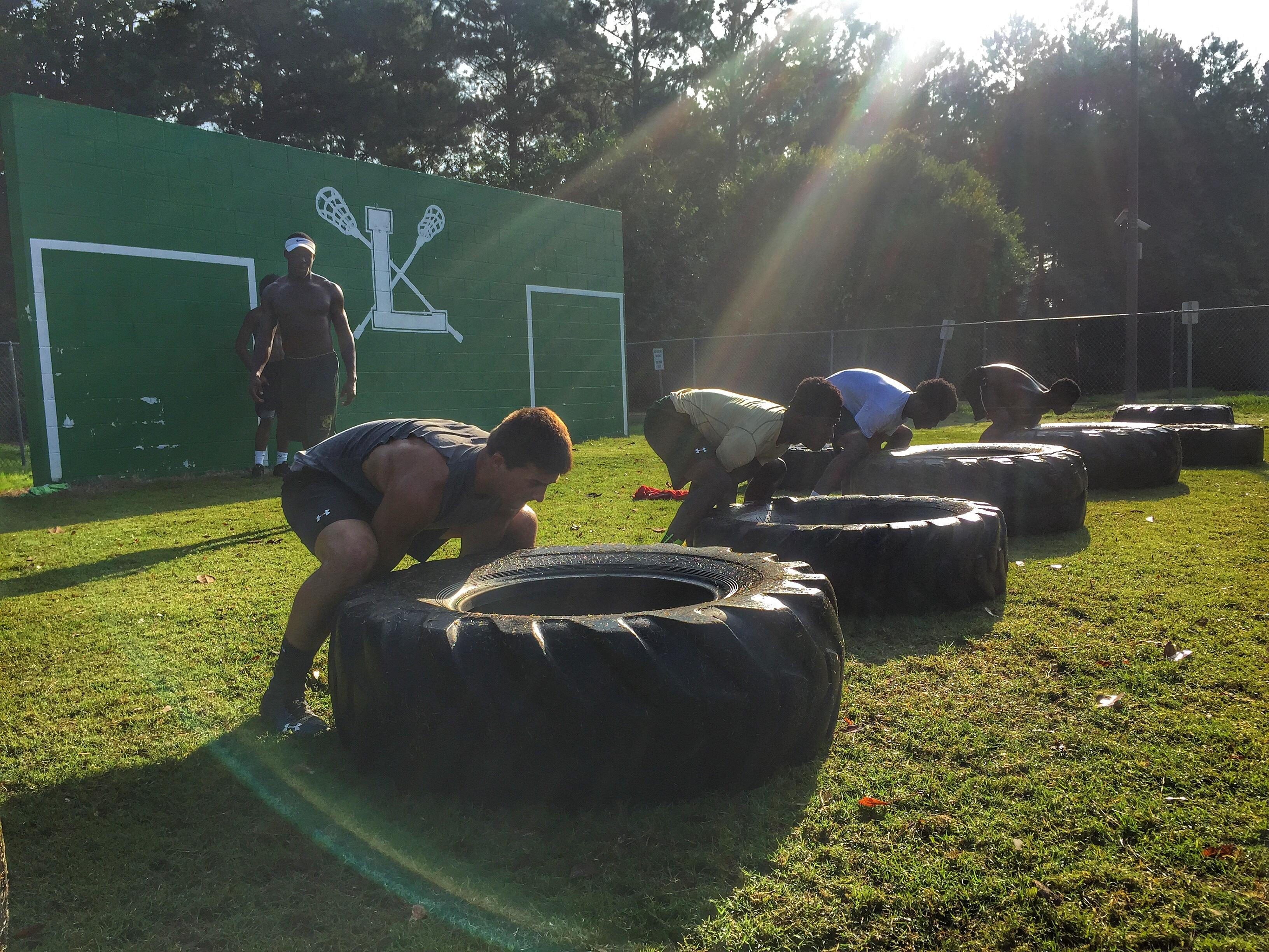 """Lincoln Trojans football players perform tire drills during summer workouts last week, on a day dubbed """"Competition Thursday."""""""